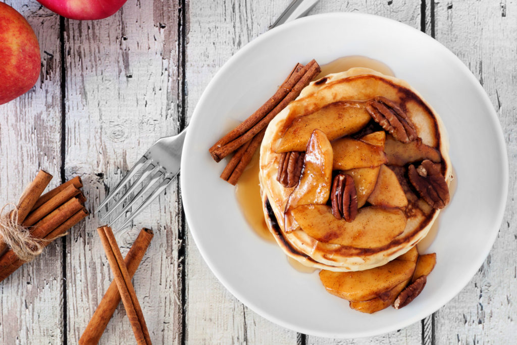 Autumn pancake stack with baked apples, pecans and cinnamon topped with maple syrup, overhead view
