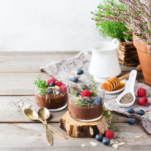 Food and drink, healthy eating and dieting concept. Homemade chocolate chia pudding with fresh berries and green thyme for breakfast on a cozy kitchen table. Copy space background