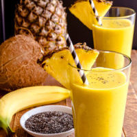 Fresh blended fruit smoothies made with pineapple, banana, coconut, turmeric and chia seeds surrounded by raw ingredients in drinking glass with pineapple slice garnish and blue swirled straw