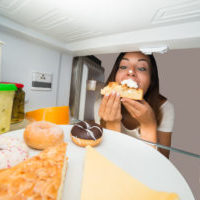 Young Woman Eating Slice Of Sweet Cake In Refrigerator