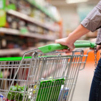 Young woman with pushcart in supermarket looking for groceries