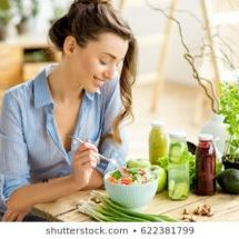 young-happy-woman-eating-healthy-260nw-622381799